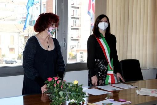 Due donne a un tavolo, una con fascia tricolore