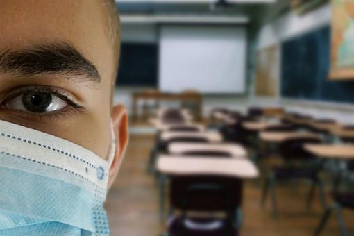 persona in primo piano con mascherina di fronte a un'aula scolastica vuota